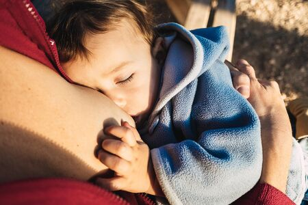 Baby naps while being breastfed by his mother outdoors.