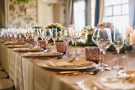 Länglicher Tisch mit dem elegant arrangierten Besteck und schönen Mittelstücken, ideal für die Dekoration einer Hochzeit.
