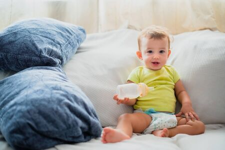 Baby in shirt play with his formula milk bottle satisfied and smiling looking at camera.
