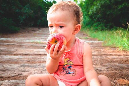 One year old baby sitting in a forest feeding in a paleo way, biting an apple.
