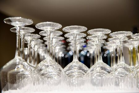 Empty wine glasses stacked on a barmans table, illuminated at night, for a party. 스톡 콘텐츠