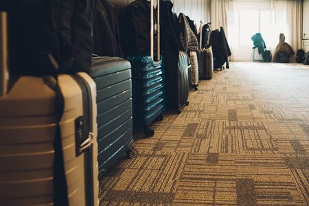 Travel suitcases lined up in a spacious hotel room of Asian tourists, with copy space.