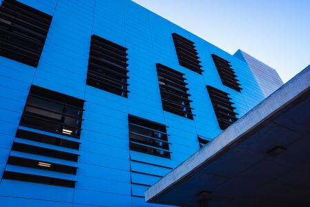 Industrial office building in simple and simple style with smooth walls, blue background and copy space. Imagens
