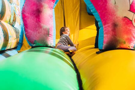 Child sliding down a colorful inflatable bounce castle having a great time. Standard-Bild