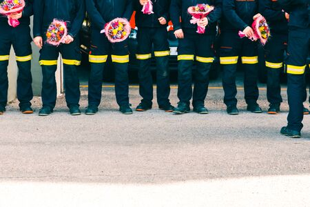 Group of firefighters with bouquets to give to their partners in a tribute.