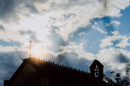 Cross on top of a church, backlit by the sun, concept of spirituality. Banco de Imagens