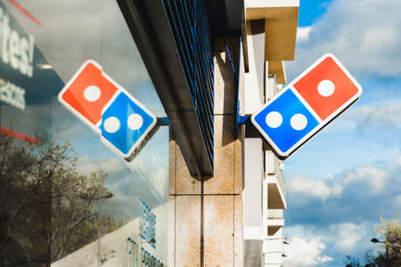 Valencia, Spain - March 5, 2020: Dominos pizza restaurant, with its logo reflected on the glass, in the financial area of Valencia.