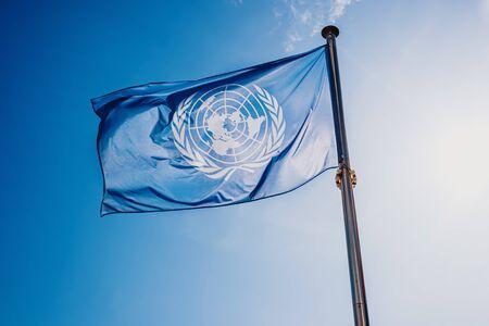 UN flag waved against the sun and blue sky. Foto de archivo