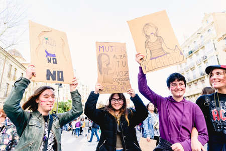 Valencia, Spain - March 8, 2020: Strong slogans about machismo in banners carried by women in a feminist demonstration.