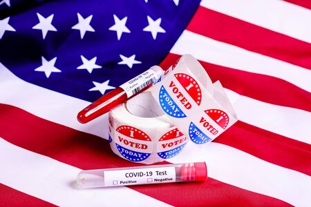 Test tubes with covid-19 test on American flag in the presidential elections.