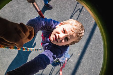 Boy goes down with a rope from a play tower in a park. Stock Photo