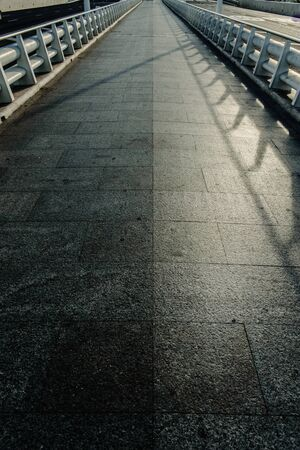 A long marble tile road with white metal railings with a vanishing line on the horizon, empty with nobody, concept of direction alone.