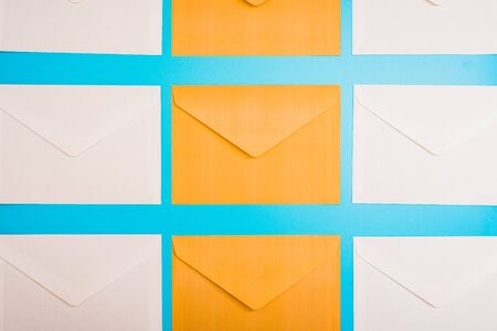 Repetitive background with orange and blue paper envelopes on a stationery office table that sends letters. Imagens