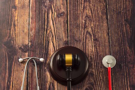 Gavel and stethoscope on wooden background, dark environment. Stock fotó