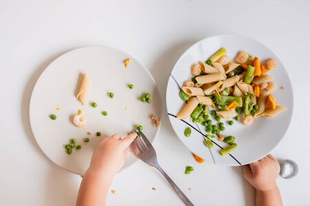 One-year-old baby eats the food from his plate directly with his hands.