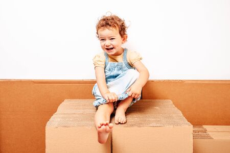 Portrait of girl sitting on stack of cardboard