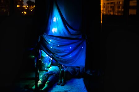 Two children read a digital story on a tablet hidden under a sheet-built fort in their living room before bed. Stockfoto