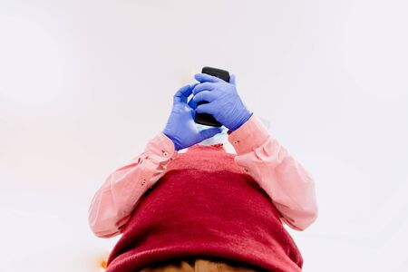 Man with latex gloves manipulates his mobile phone.