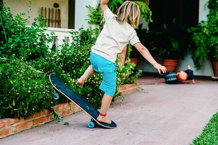 5 year old boy practicing skate in his backyard, stumbling and falling to the ground.
