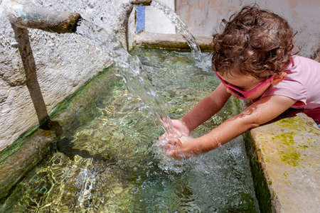 A 1-year-old girl refreshes herself with fresh water from a fountain in a small village on a summer day.