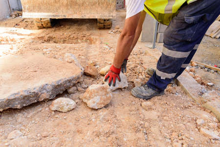 Gloved worker removes a rock from the road on a construction site.