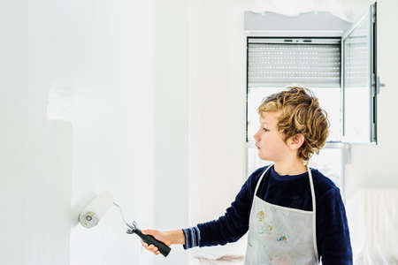 Boy helps his family paint a white wall.