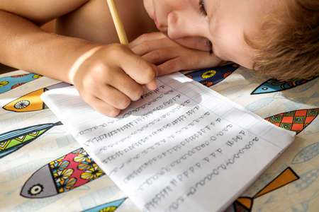 Boy tries to study and do his homework during the summer holidays. 免版税图像