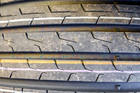 Focused on closeup of new car tires with tread marks for good traction.