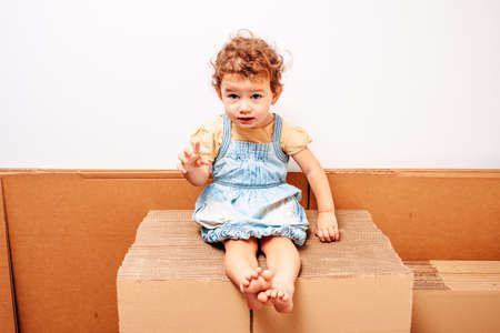 Face of smiling girl looking at camera on cardboard, with white background