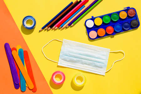 School supplies next to a face mask, flat lay background back to school.