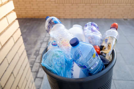 Valencia, Spain - August 4, 2020: Many plastic bottles overflowing in a street litter bin. Material that will not be recycled properly.