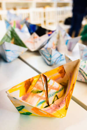 Homemade paper boats decorated with colors for children a day of crafts.