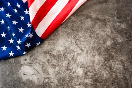 Striking colored American flag isolated in a corner on a stone gray background.