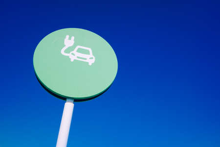 Round sign of electric car recharging station, with blue sky background and copy space. Foto de archivo