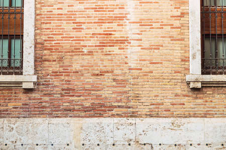 Brick wall between two old windows, background with copy space to place text. Reklamní fotografie