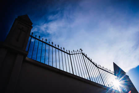 Metal grating of a cemetery with a cross on a white wall, copy space and deep and vibrant blue sky background.