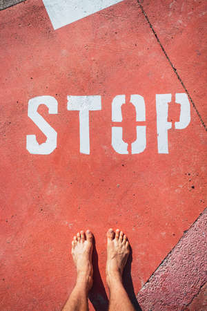 An illegal immigrant stands barefoot at a stop sign on the ground.