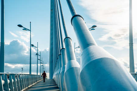 Person walks on an industrial bridge with large pylons and cable ties.