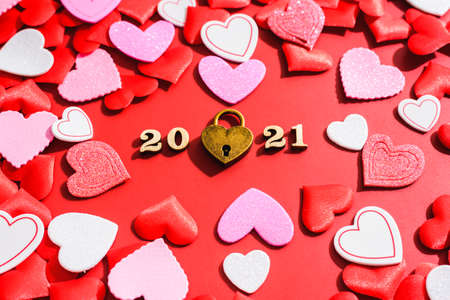 Love padlock on a red background with hearts for Valentine's Day in 2021.