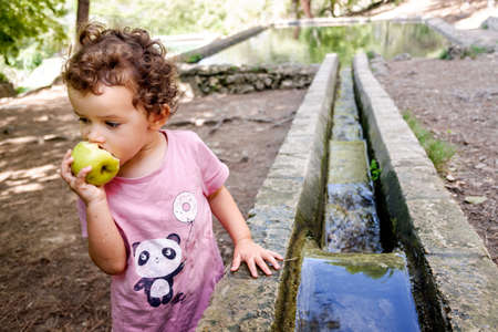 Young girl nibbling an apple during a healthy country walk. Banque d'images