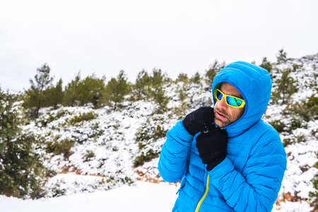 Mountaineer man with blue coat and sunglasses walking on a snowy mountain path in his spare time.