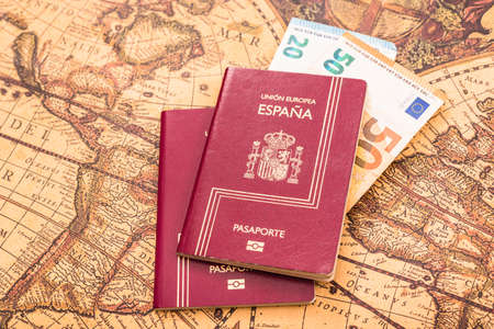Spanish passport with euro bills inside, on a world map for travelers.