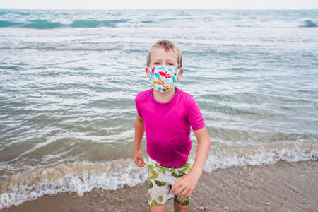 Portrait of a boy on the beach wearing a protective mask against viruses on vacation.