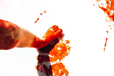 Girl paints a white canvas with paint, dirtying her hands and feet with red paint. Stock fotó