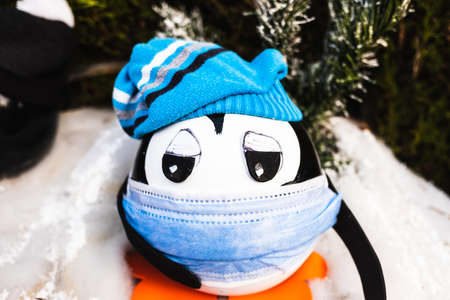 Christmas penguin dolls with a mask, sick with the flu.