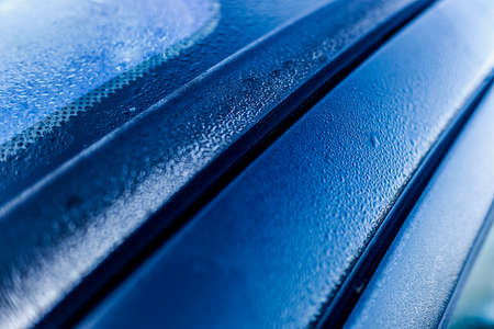Drops of water on the metallic surface of a blue car after washing it, detail. Stock fotó