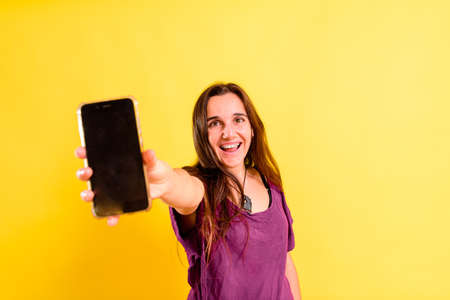 Isolated on yellow studio background a young woman holds her smartphone.