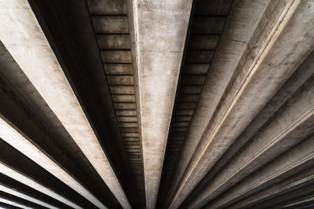 Cement beams support the weight of a bridge over a road. Stock fotó
