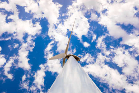 Wind turbines on top of a Spanish mountain with sky full of clouds on a summer day.