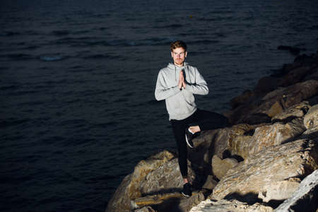 Young man by the sea at dusk practices yoga with the sound of the waves to relax.